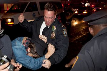 An Occupy Wall Street protester draws contact from a police officer near Zuccotti Park after being ordered to leave the longtime encampment in New York, Nov. 15, 2011