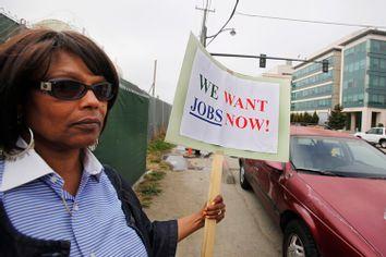 Unemployed Diana Jackson holds up sign