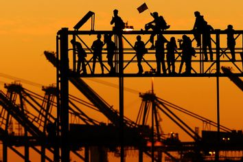 Occupy Oakland protesters stand atop a railroad scaffold at the Port of Oakland