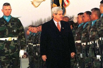 U.S. House Speaker Newt Gingrich (C) reviews U.S. military honor guards upon his arrival at a U.S. air base in Osan, South Korea, March 24, 1997.