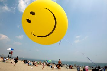 A smiley-face ballon floats over Revere Beach in Revere, Mass.