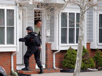 A man looks out of his door as a SWAT team member knocks on his neighbors door as they search for the remaining suspect in the Boston Marathon bombings in Watertown