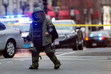 Law enforcement bomb technician walks away after preparing controlled detonation of a suspicious object during a search for a suspect in the Boston Marathon bombing, in Boston