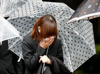 Mourner cries after sending off hearse carrying coffin of twenty-one-year-old Mai Muto in Tokyo