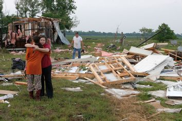 Leah Hill, of Shawnee, Oklahoma, is hugged by friend Sidney Sizemore, as they look through Hill's scattered belongings from her home which was destroyed by a tornado on Sunday, west of Shawnee, Oklahoma