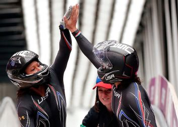 Pilot Elana Meyers and Lauryn Williams of the U.S. high-five after completing a run in the women's bobsleigh competition at the 2014 Sochi Winter Olympics