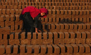 Farzeena arranges bricks to be baked in a kiln at a brickyard in the outskirts of Islamabad