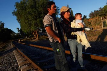 An illegal Salvadoran migrant couple is seen on railway track with their son Andrew, six months, during the arrival of the