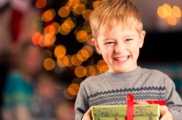 Excited young boy holding Christmas gift in front of tree