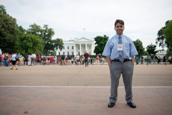 Kyle Mazza stands for a portrait in front of the White House.