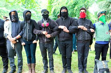 'Antifa' protesters link arms as they demonstrate at a rally