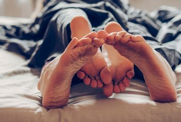 A couple's feet in bed