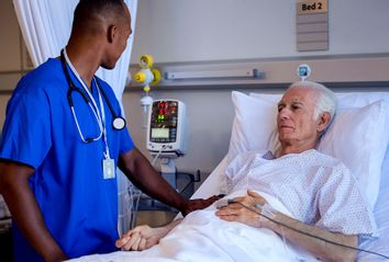 Male nurse doing routine checkup of senior patient in hospital room
