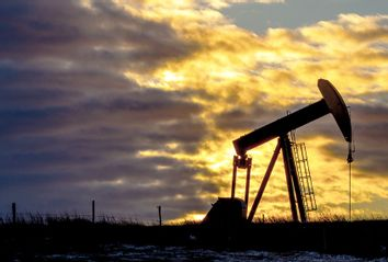 Pumpjack at oil industry against cloudy sky during sunset in North Dakota, USA