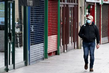 A man wearing a surgical face mask walks passed closed shops