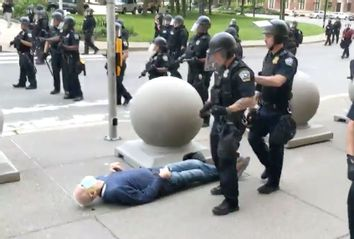 An elderly man is knocked to the ground by two police officers