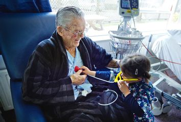 Small girl measuring heart beats to her sick grandfather with a toy stethoscope