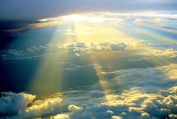 Golden sun rays beaming through white clouds