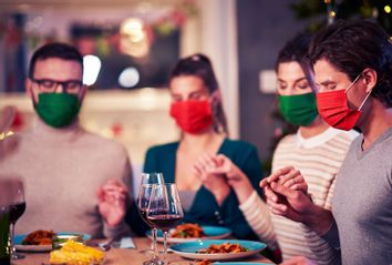 Group of friends in masks praying over Thanksgiving table at home