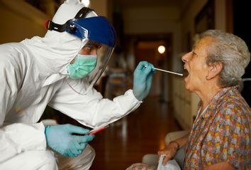 Doing a COVID test in full PPE wear at a senior's home