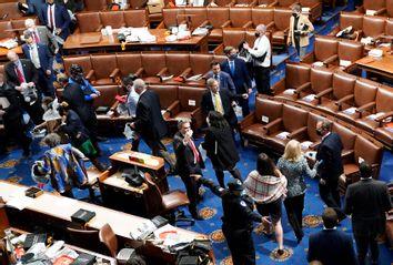 Members of Congress evacuate the House Chamber