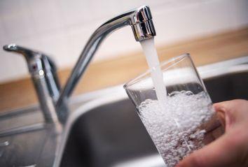 A man holds a glass under a running tap