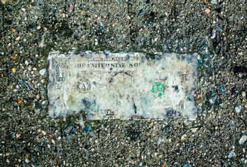 Deteriorating one dollar bill on wet pavement