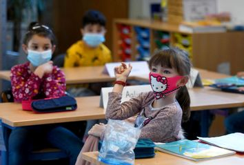 Second-grade pupils wear face masks as they attend school lessons