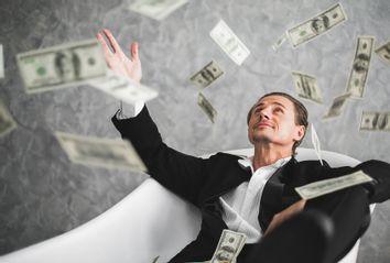 Man throwing dollar bills in a bathtub