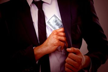 Cropped image of a businessman putting money