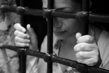 Young woman behind prison bars