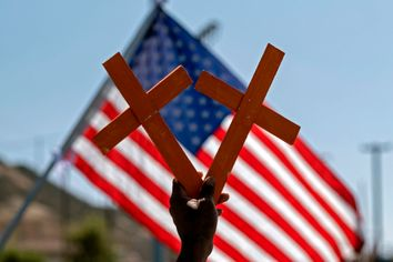 crosses in front of a US flag