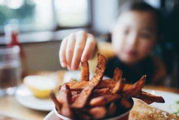 Little girl reaching for fries in a restaurant