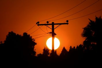 The sun sets behind power lines in Los Angeles, California