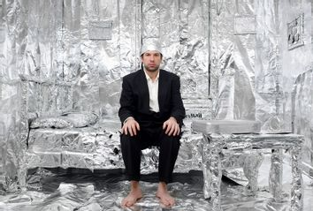 Man in tinfoil hat and tinfoil-lined bedroom