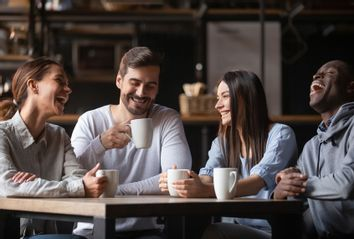 Happy friend group chatting laughing drinking coffee in cafe