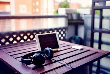 Improvised desk on the balcony, with a wooden table, a digital tablet and headphones