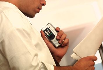 Man holding sheets of paper and a cassette recorder