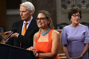 Sen. Kyrsten Sinema, D-Ariz., center, answers questions from members of the press after a procedural vote on a bipartisan infrastructure bill on July 28, 2021.