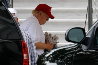 Former President Donald Trump thumbs through a stack of newspapers.