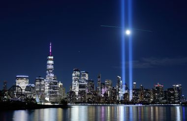 A passing helicopter creates a cross through the beams of the Tribute in Light as it is tested over lower Manhattan and One World Trade Center in New York City
