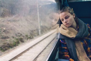 Woman looks outside a train window while traveling
