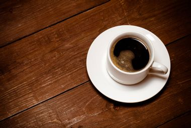 White cup of coffee on old wooden table