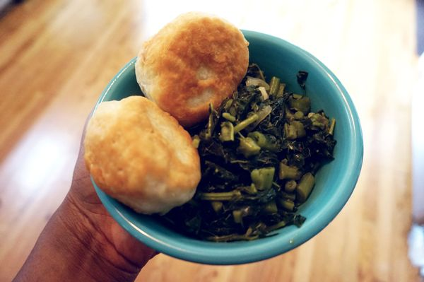 Bowl of cooked calalloo with fried dumplings