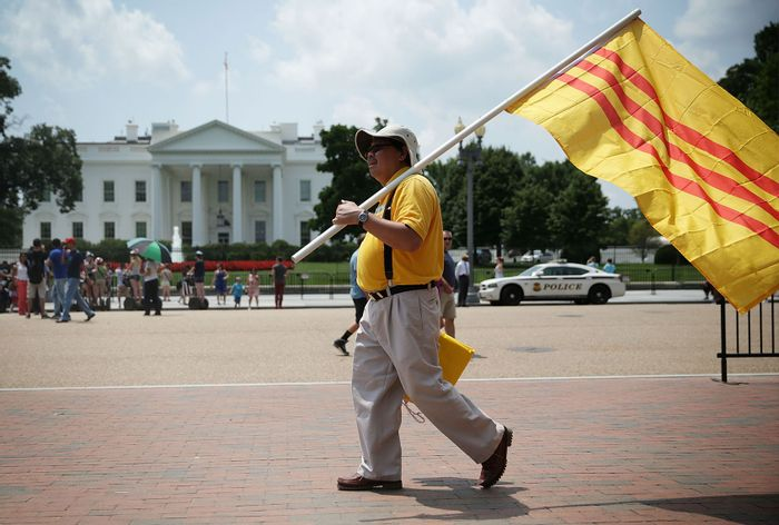 Vietnamese-American activist holds a South Vietnam flag as he participates in a protest outside the White House