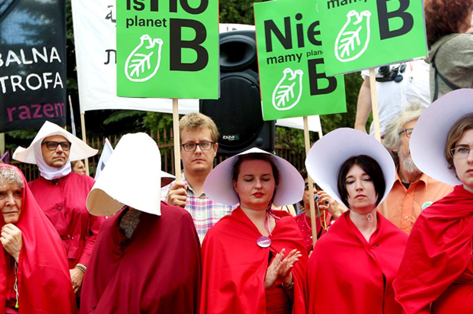 """Women dressed as """"handmaids"""" protest Trump during his Poland visit"""